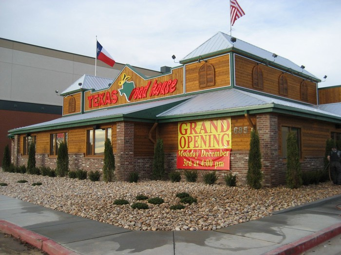 Texas Roadhouse location with grand opening sign and gravel front lawn, along with U.S. and Texas flags flying.