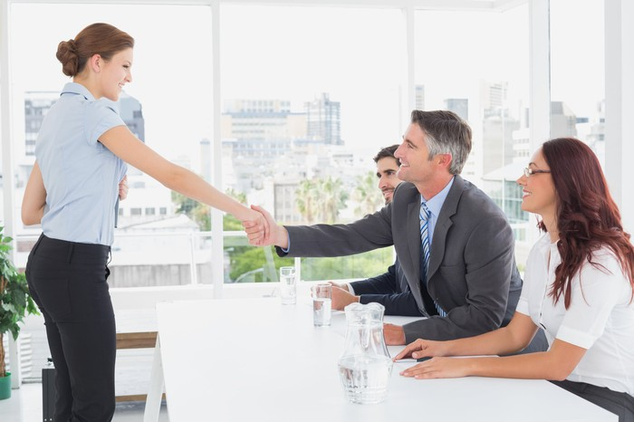 A job applicant shakes the hand of a seated interviewer, flanked by two other interviewers.