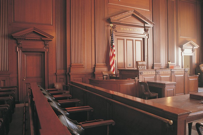 A courtroom from the perspective of the jury box, with a view of the judge's chair and front of the courtroom.