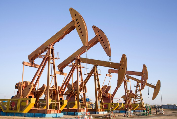 A row of oil pumps in a desert landscape.
