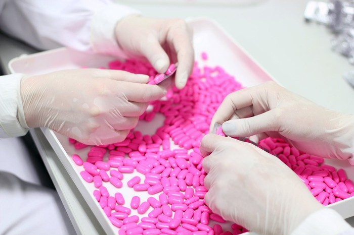 Two sets of gloved hands press a pile of pink pills into packages.