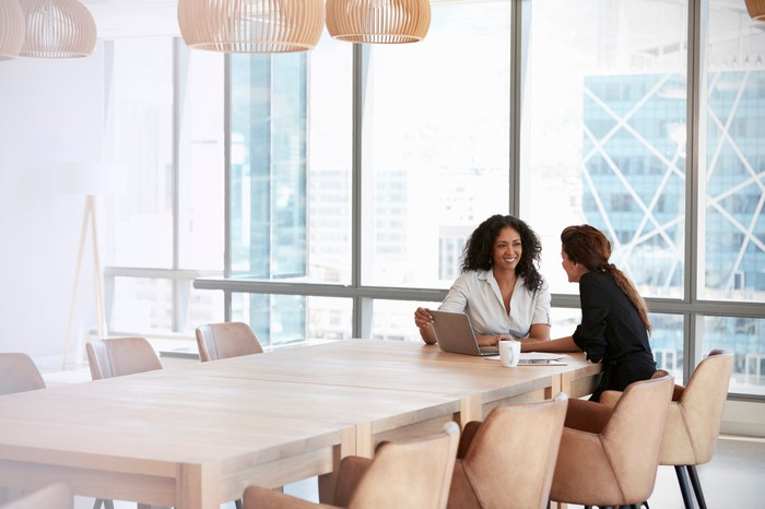 Two businesswomen using laptop in boardroom meeting.