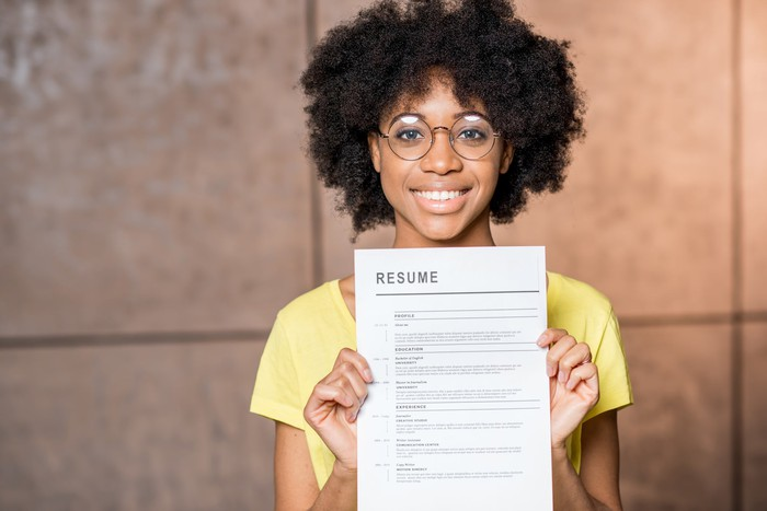 Woman holding up a resume.