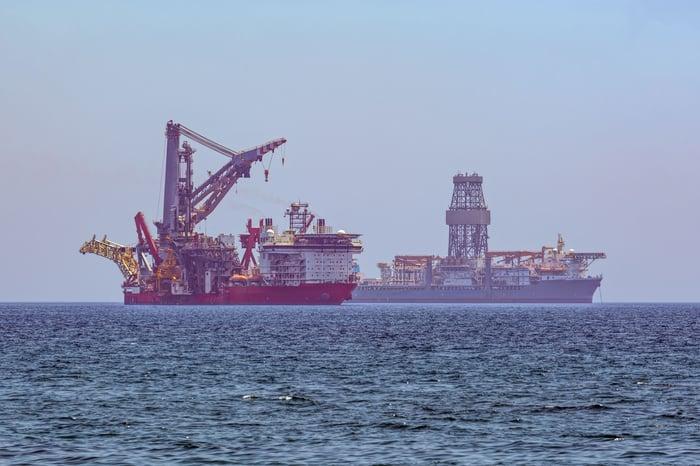 Drill ship and service vessel at sea.