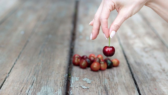 A hand picking a cherry from a table.