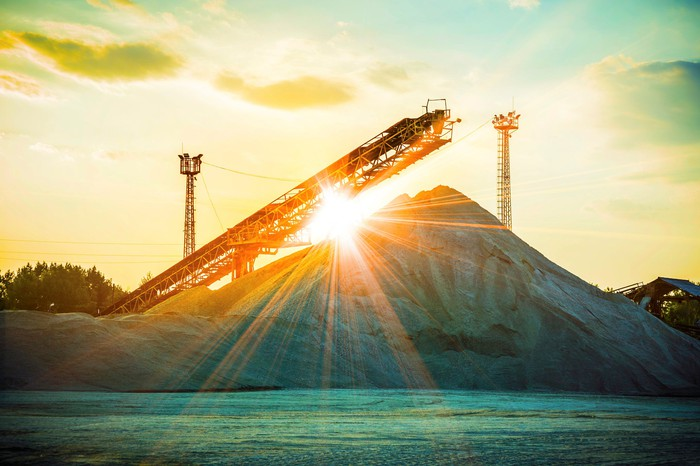 A pile of sand with the sun shining in the background.