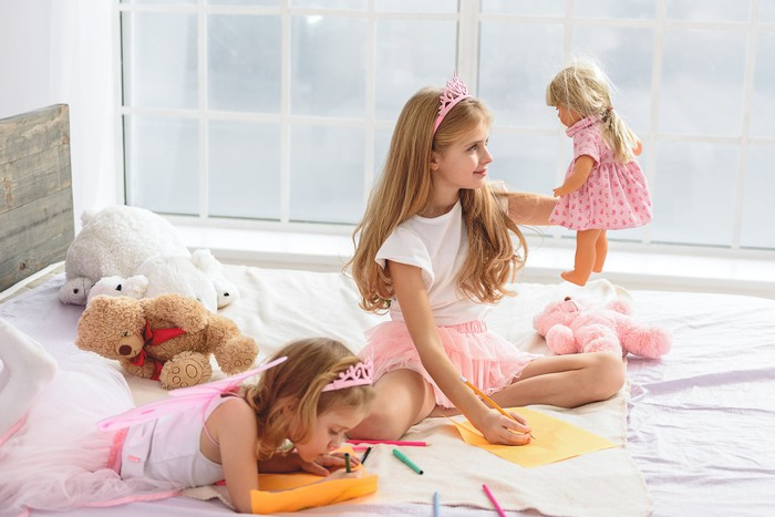 Girls playing with a doll while coloring