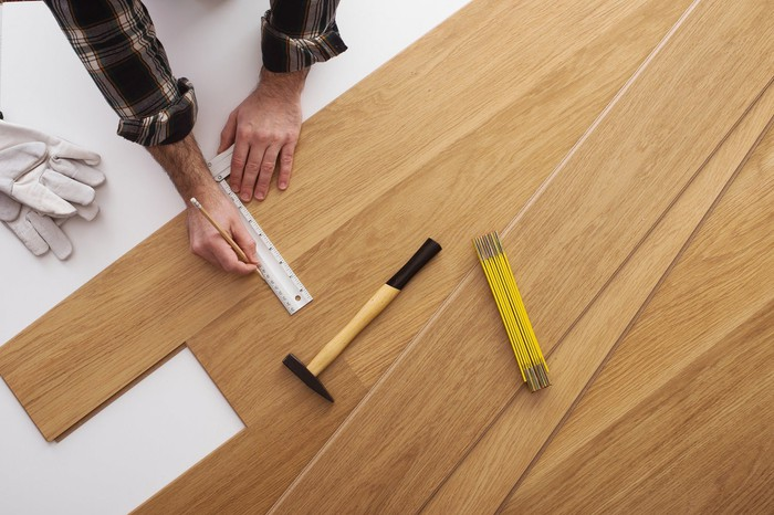 A man measuring and marking a piece of hardwood flooring to cut.
