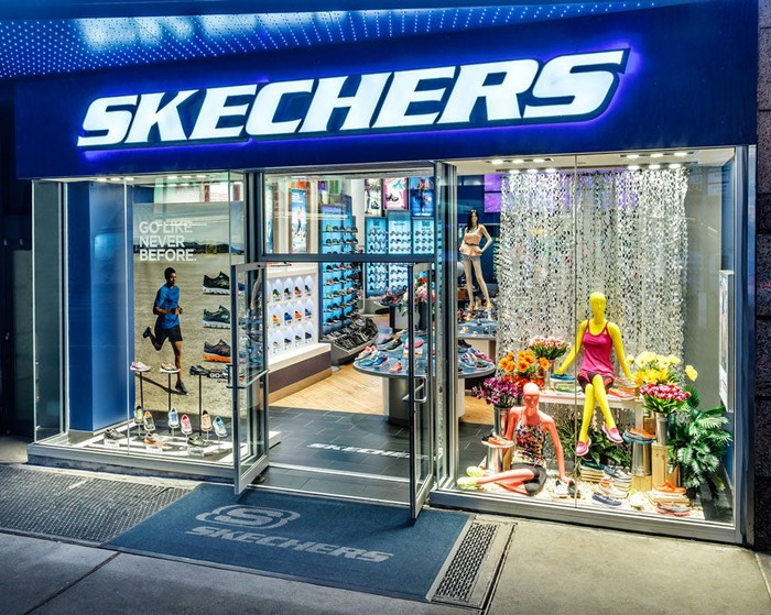 Looking into a Skechers store from the outside with a brightly lit glass front.