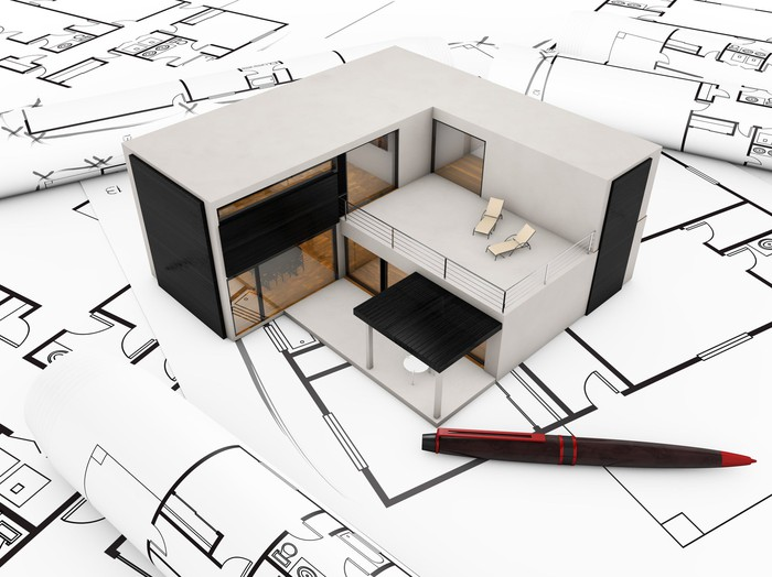 Modular building with computer-aided-design drawings around it.