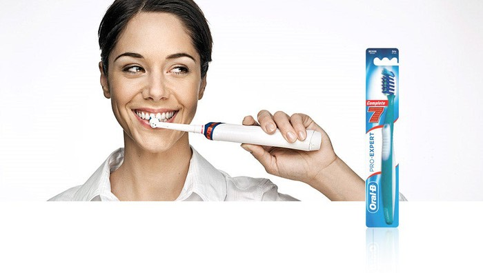 Woman brushing teeth with Oral-B toothbrush