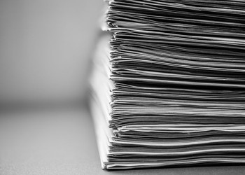 Newspapers Stacked in a Tall Pile, Isolated on White