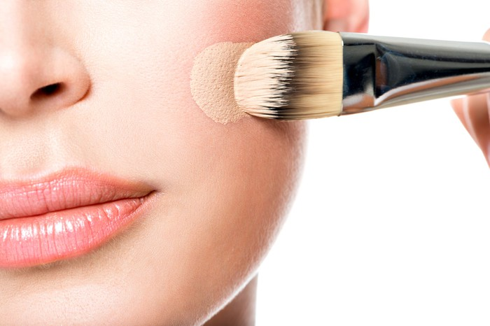 A woman putting foundation on her face
