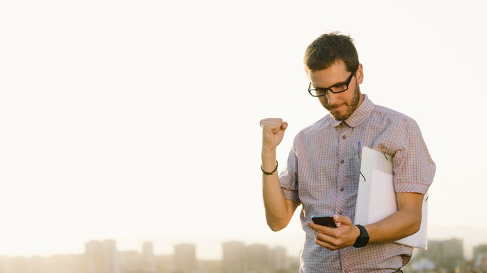 Man holding up fist and looking at phone