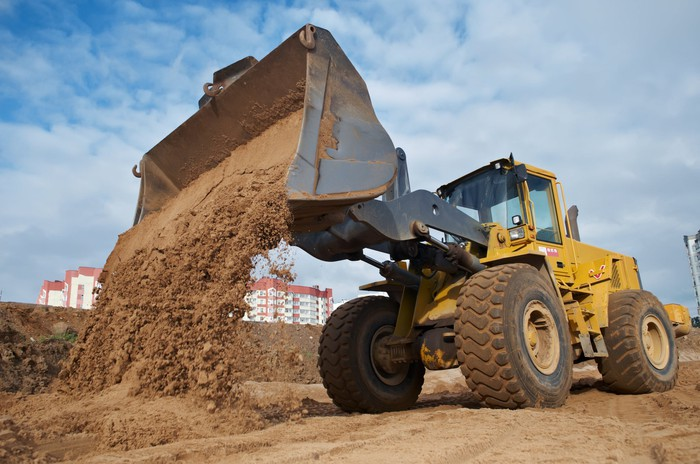 Excavator dumping sand into a pile.