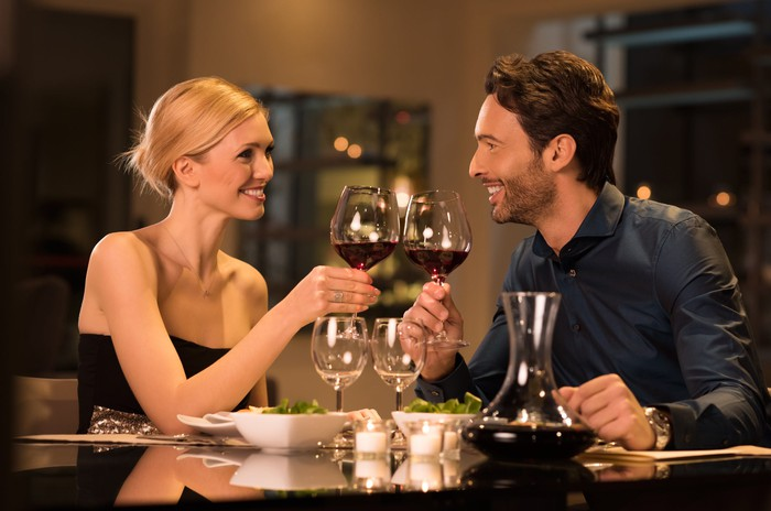 Dressed-up couple toasting over red wine at restaurant