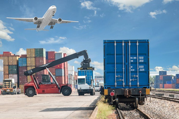 Shipping container being transferred from truck to freight train, with freight aircraft taking off in background.