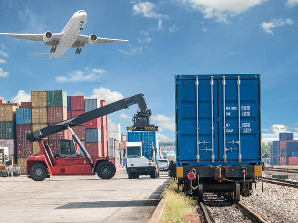 Loading Shipping Container onto Train, With Plane in Background