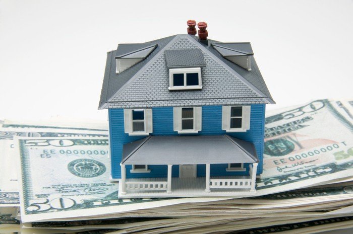 a small model house sitting on a stack of fifty dollar bills