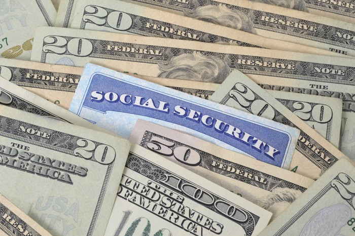 A Social Security card nestled among U.S. currency bills