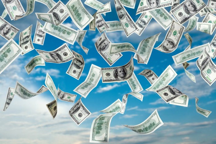 u.s. currency bills floating down from a blue sky
