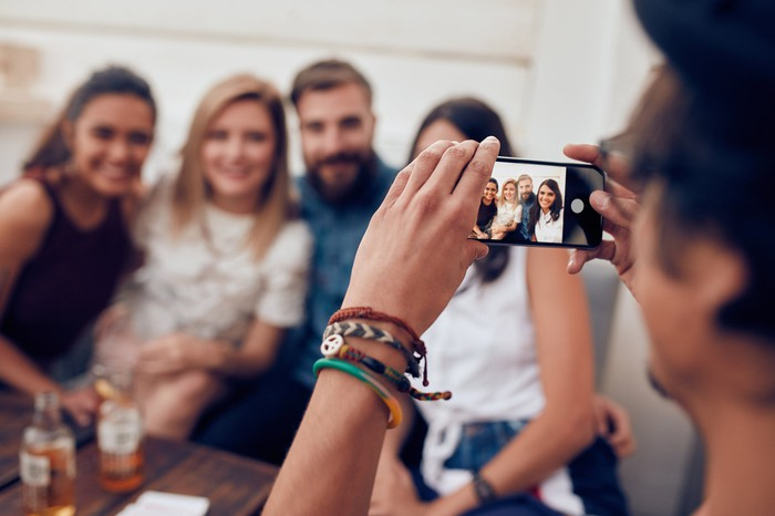 young man taking photo of four friends with smartphone