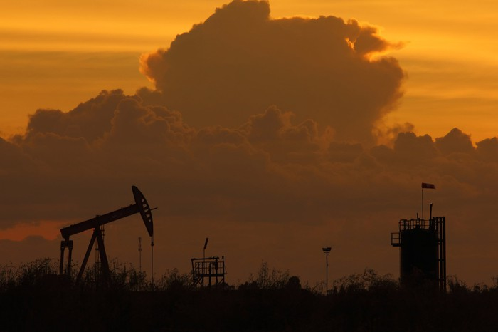 The silhouette of an oil pump at dusk with clouds in the background.