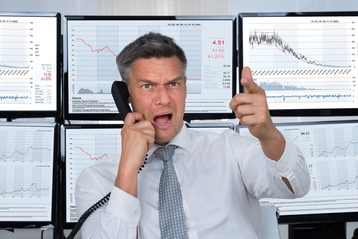 Angry man in front of six monitors displaying stock charts.