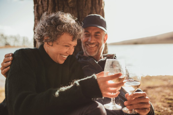 An older couple enjoying a glass of wine outside