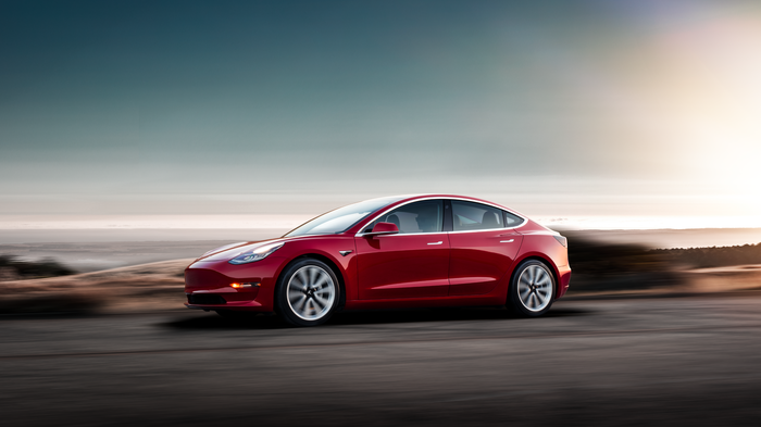 Red Model 3 driving with a sunset in the background