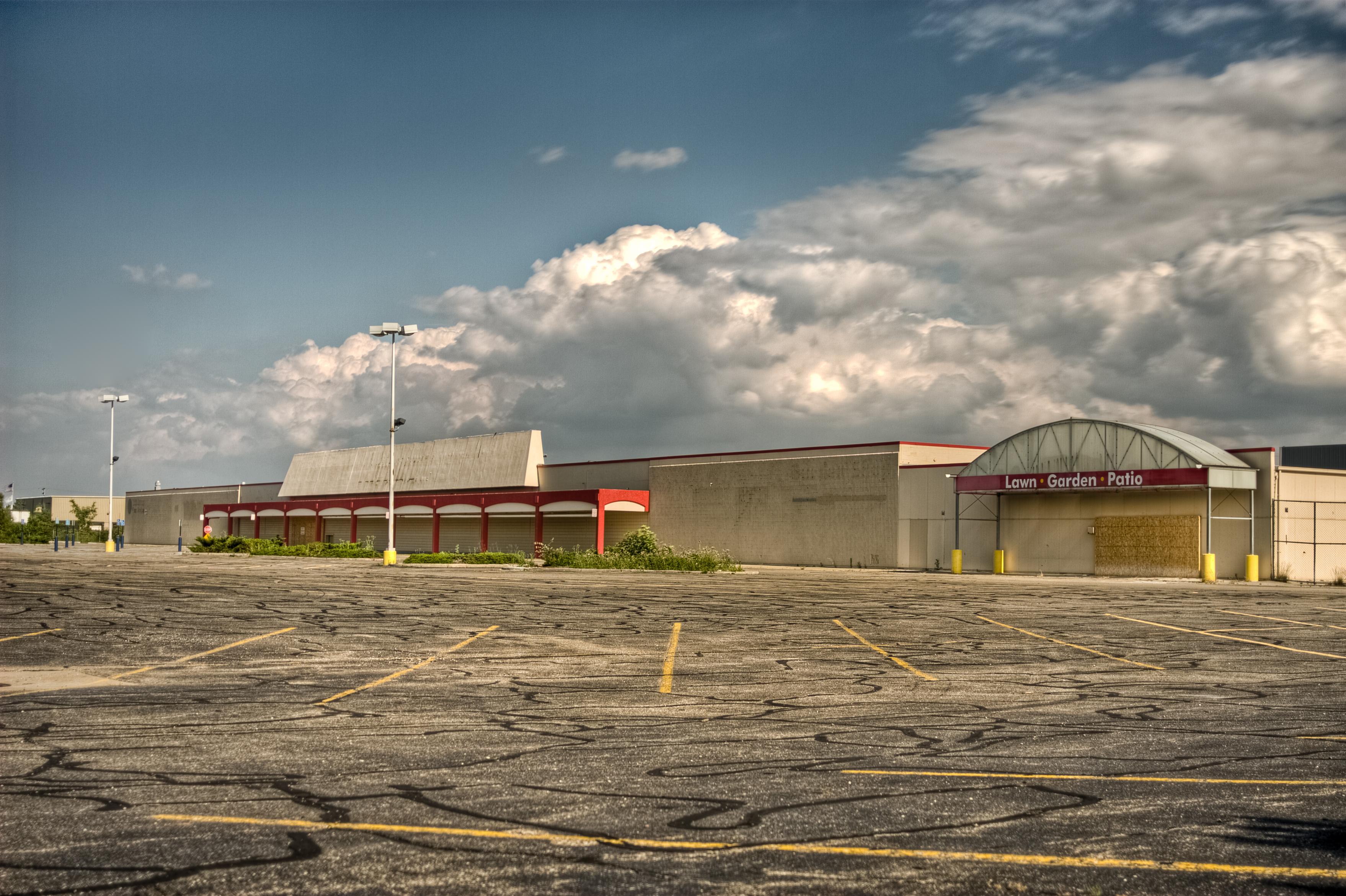 An abandoned shopping center, as seen from across a crumbling parking lot.