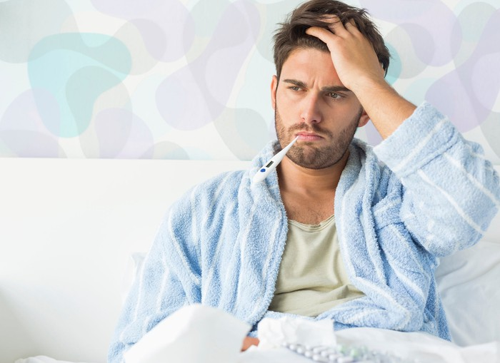 Man sick in bed holding his head with a thermometer in his mouth