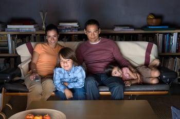 ethnic family watching tv on sofa