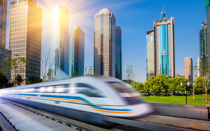 A commuter train in Shanghai passing tall buildings