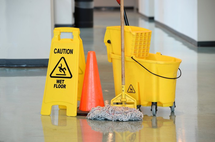 """Yellow bucket and mop on floor next to a """"caution"""" sign and orange cone."""