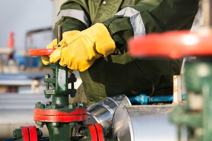 Gloved hands on a pipeline valve.