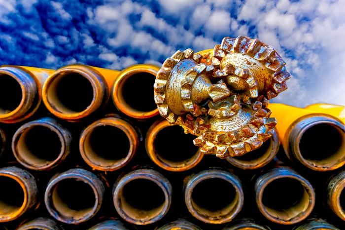 An oil-drill bit sitting atop a stack of large pipes
