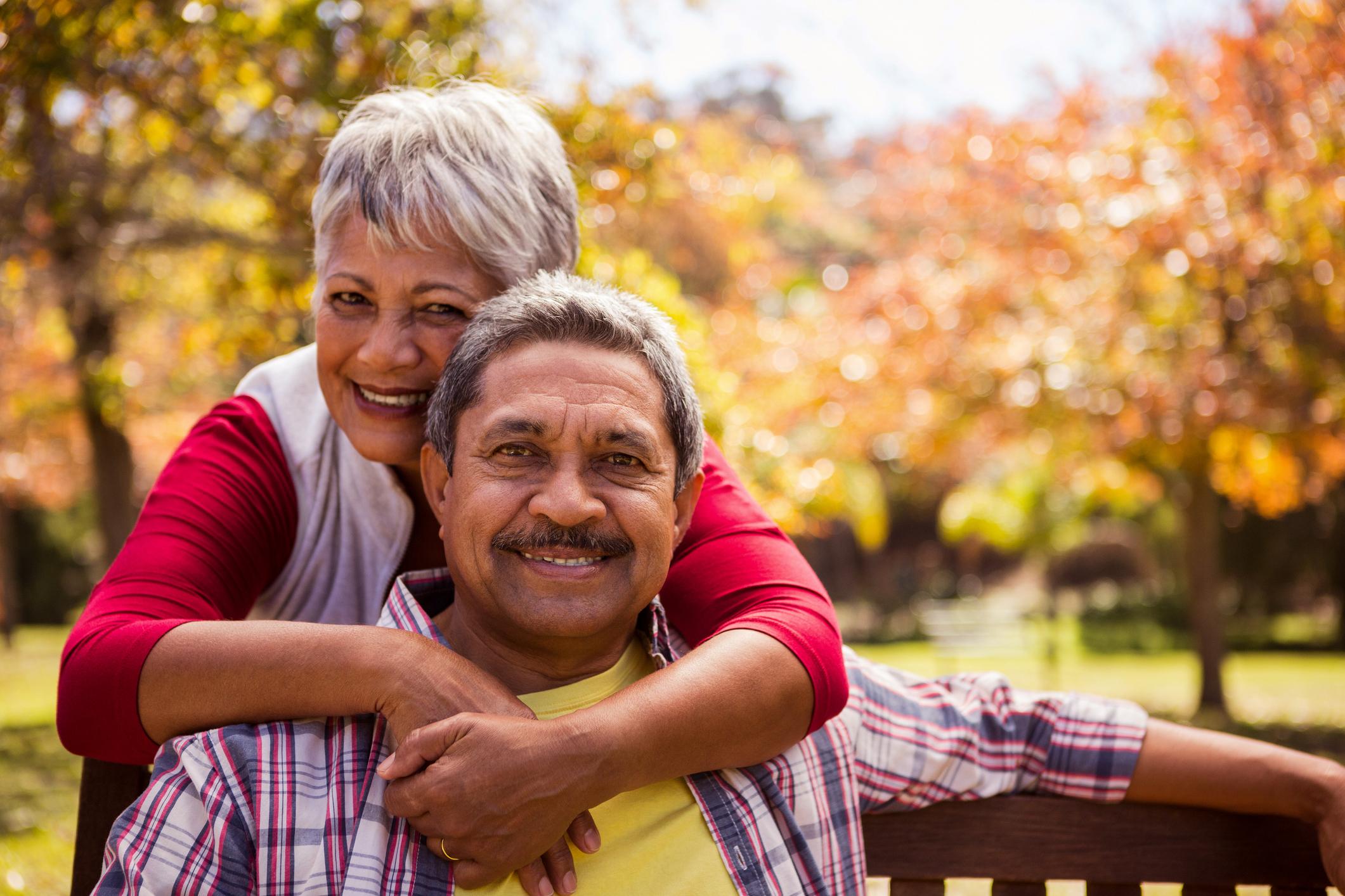 Senior woman putting arms around senior man outdoors