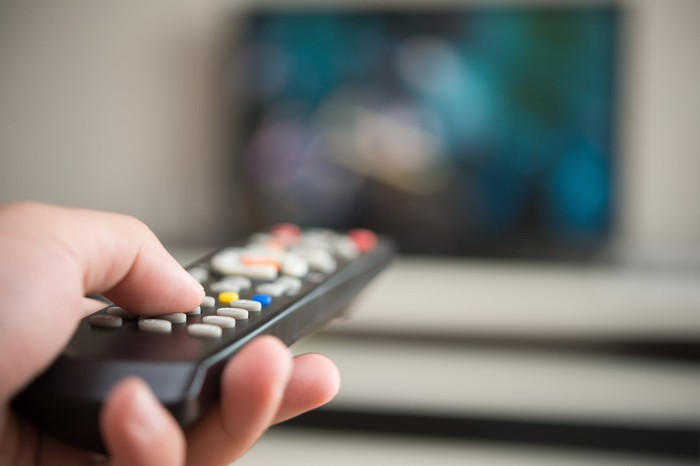 Close-up on a hand holding a TV remote, pointed at a blurry TV set in the background.