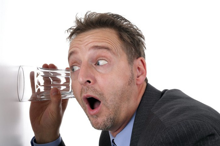 A man in a suit eavesdropping by listening through a wall with a drinking glass.