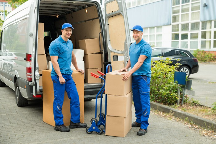 Two men removing large boxes from a van.