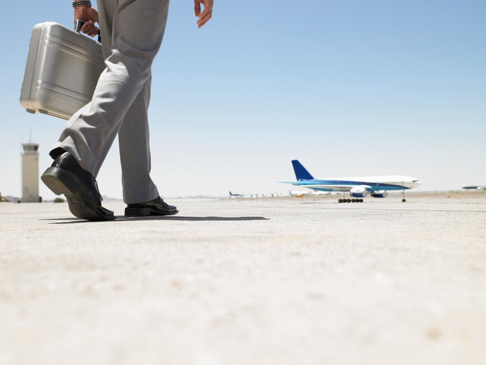 Legs of a businessman walking to an airplane with a suitcase.
