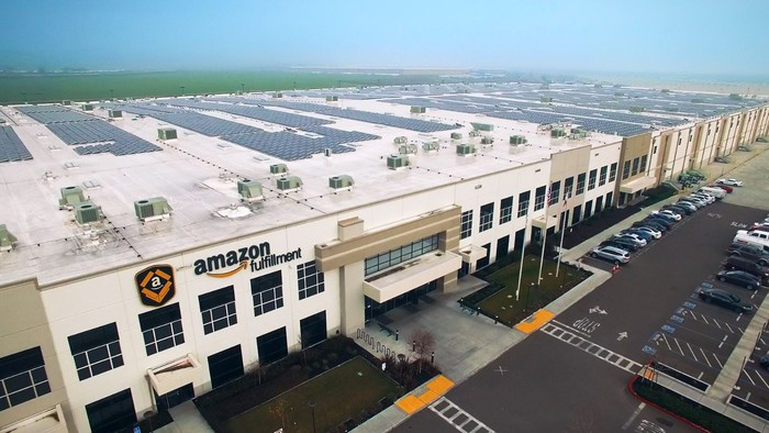 The exterior of an Amazon fulfillment center, with solar panels on the roof
