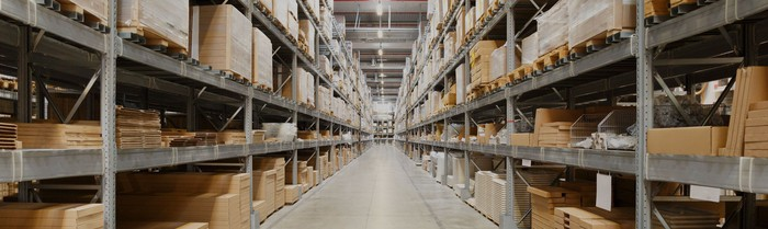 Aisle in warehouse with shelves containing pallets going up to the ceiling and bright overhead lights.