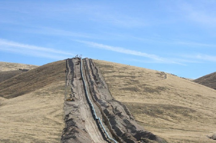 Pipeline trench being dug by heavy equipment across a hilly grassland landscape.