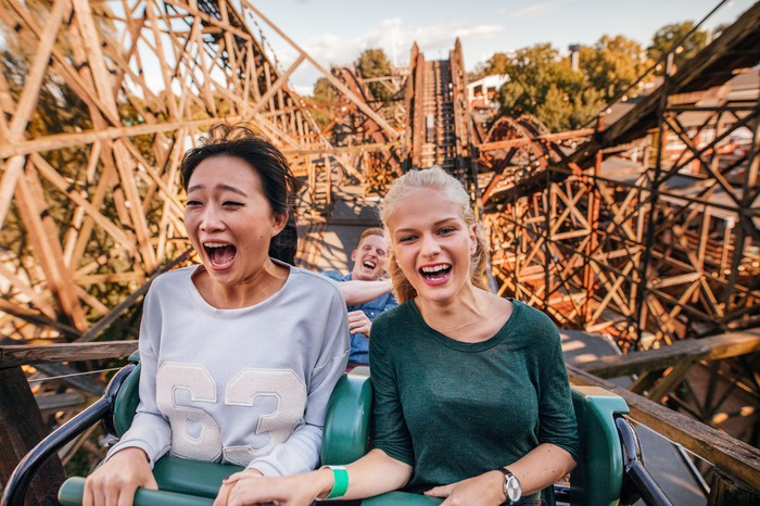 Two young women and a man riding a wooden roller coaster