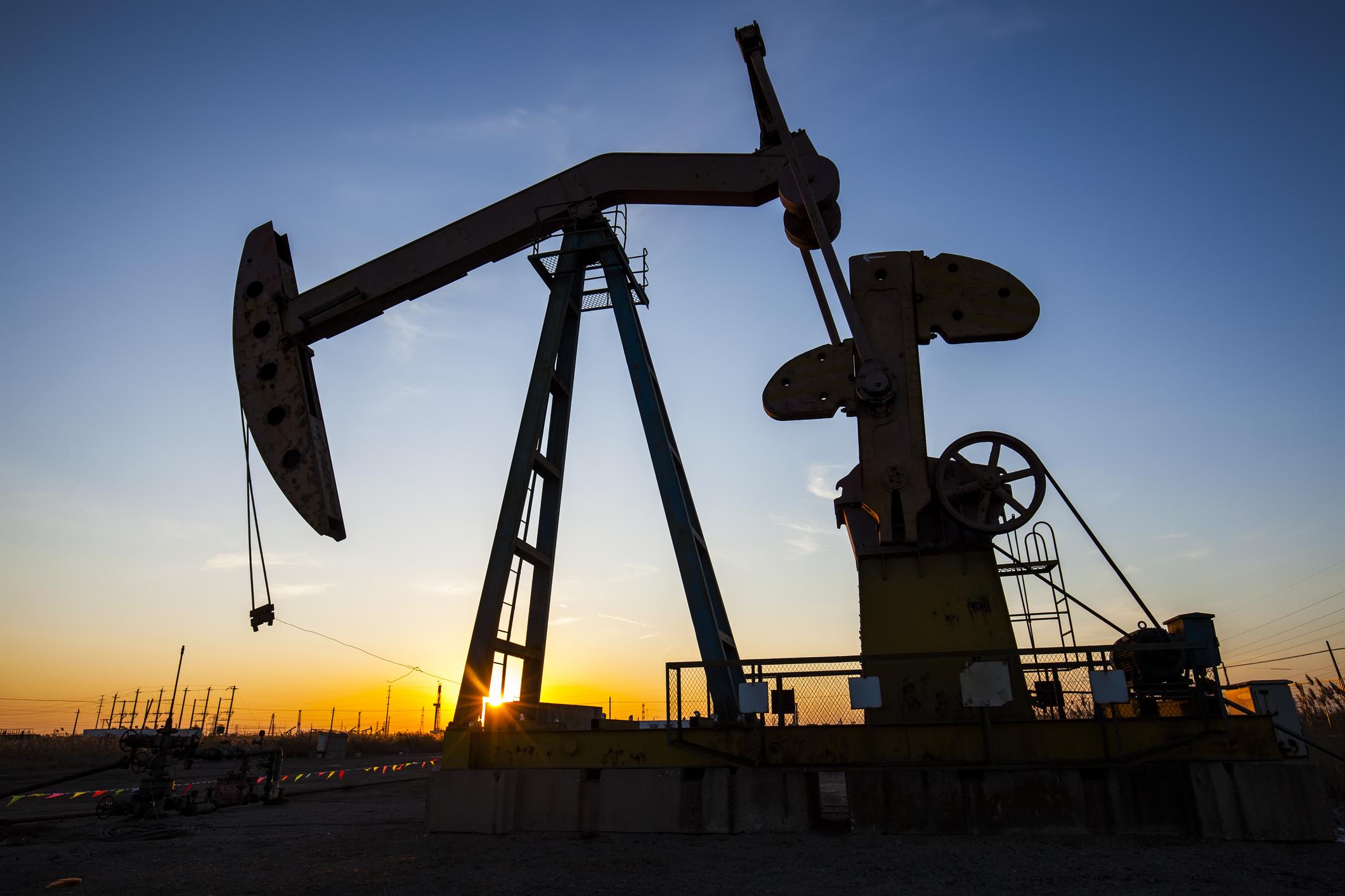 A beam of light shining through an oil pump at sunset