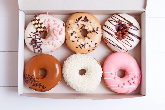 Six colorful donuts in a box.