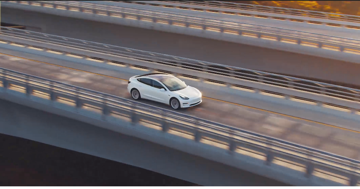 A view from above and somewhat to the side of a white Model 3 driving across a long and high bridge.