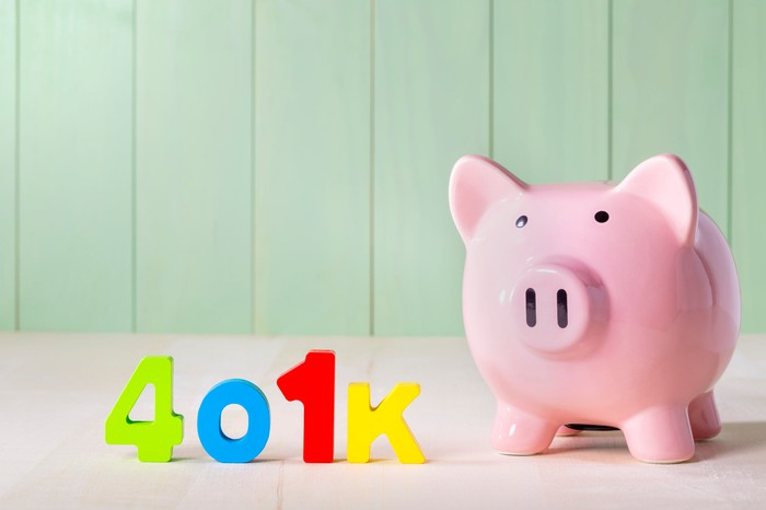 Colorful letters spelling out 401k next to a piggy bank